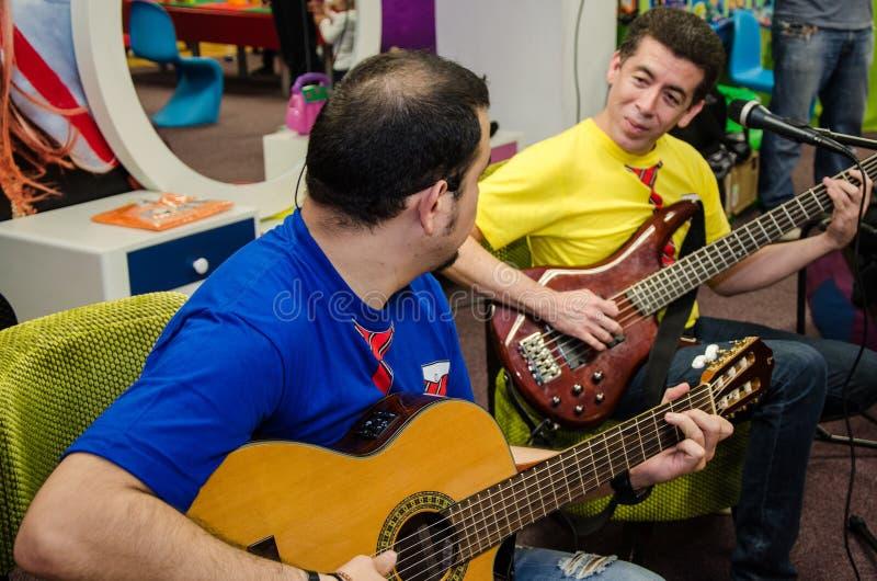Banda di duo dei chitarristi che cantano le canzoni per i bambini fotografia stock libera da diritti