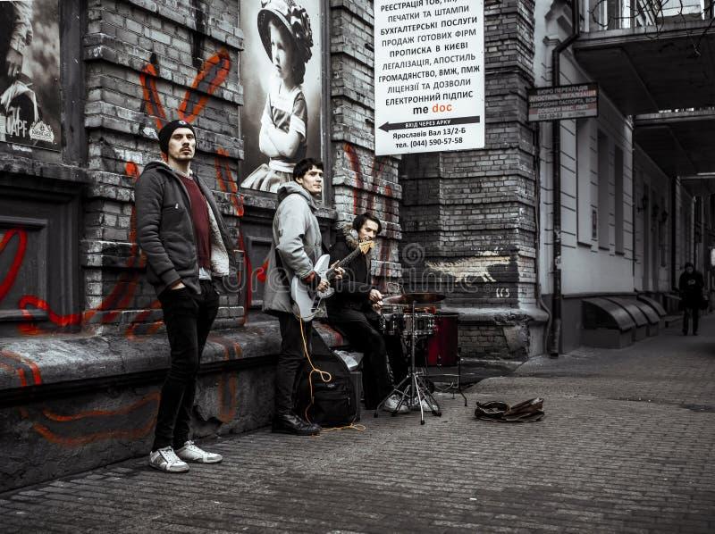 Banda di musica di tre uomini che gioca e che canta sulla via immagine stock
