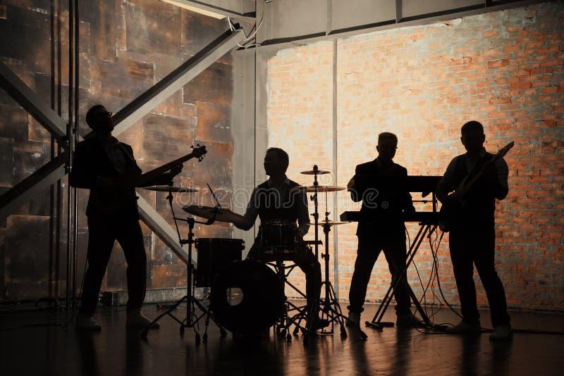 Banda e modo di musica Giovani bei in vestiti che giocano roccia e che cantano canzone Siluette delle bande con sopra un concerto fotografia stock libera da diritti