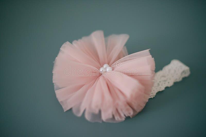 Banda principal de encaje adorable con la flor rosada grande de Tulle con las perlas o un abrigo rosado oscuro suave de la cabeza fotografía de archivo