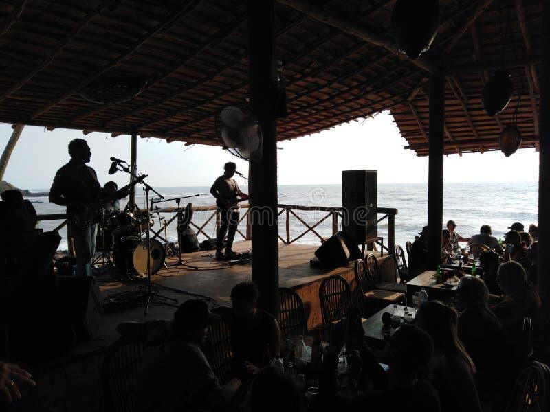 Banda que juega m?sica en un caf? por el mar Anjuna, Goa, la India imagen de archivo libre de regalías