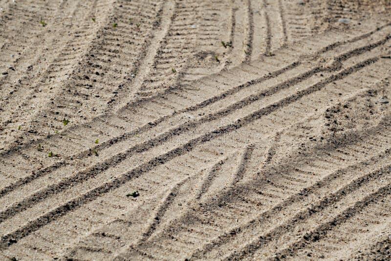 Bandafdrukken op zandige woestijnweg stock foto