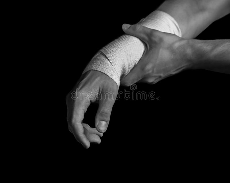 Bandaged hand, pain in the wrist. Pain in a male wrist, bandaged hand, black and white image royalty free stock image