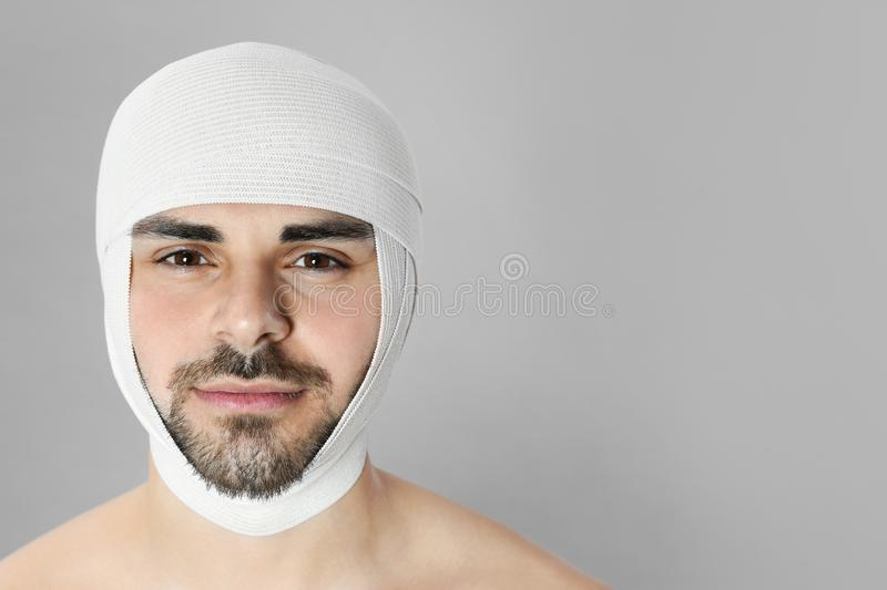 Bandaged young man after plastic surgery operation on grey background royalty free stock images
