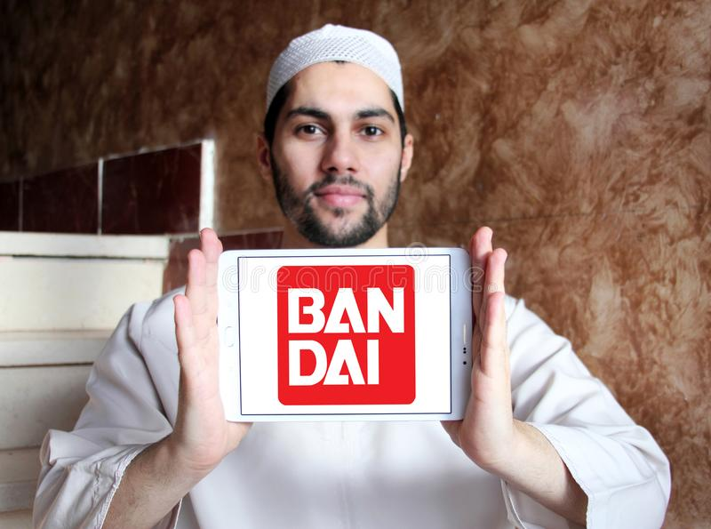 Bandai toy brand logo. Logo of Bandai toy brand on samsung tablet holded by arab muslim man. Bandai is a Japanese toy maker and a producer of a large number of stock photos