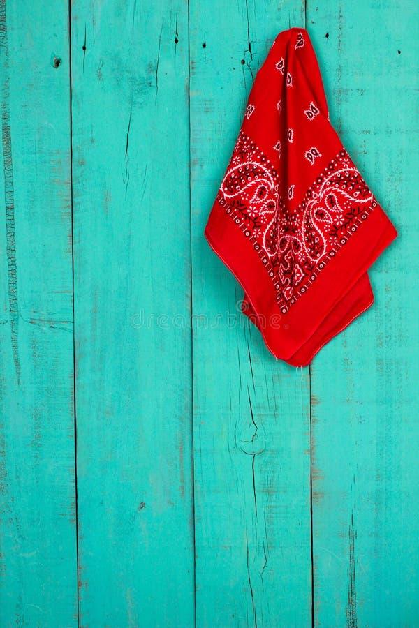 Bandana vermelho que pendura na porta de madeira azul da cerceta antiga vazia fotos de stock royalty free