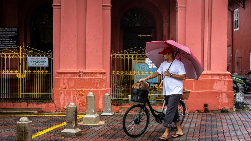 An adult man with a red umbrella in his hand walking across the Melaka street with his old bicycle. Bandar Hilir, Melaka - June 28 stock photos