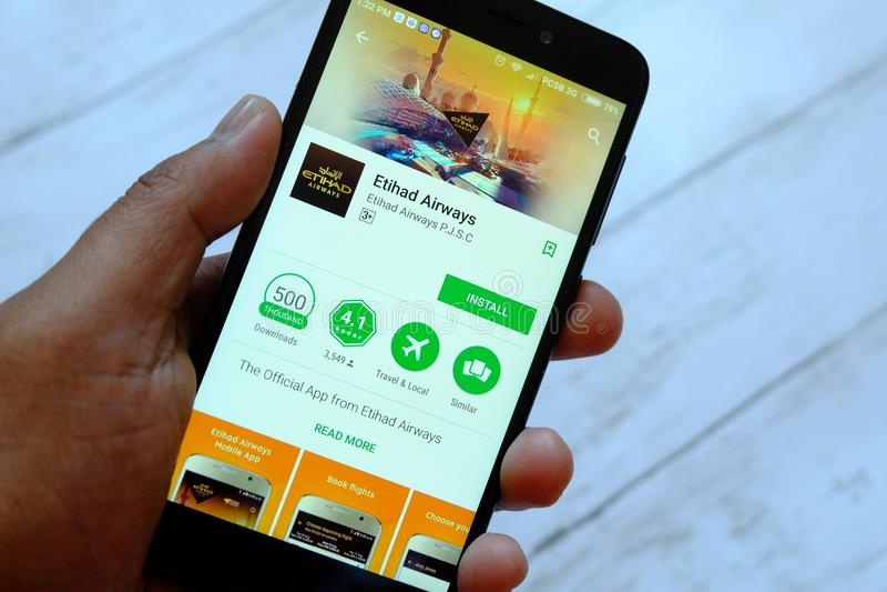 BANDAR SERI BEGAWAN, ΜΠΡΟΥΝΈΙ - 25 ΙΟΥΛΊΟΥ 2018: Ένα αρσενικό smartphone εκμετάλλευσης χεριών με τις αερογραμμές app Etihad σε έν στοκ εικόνες
