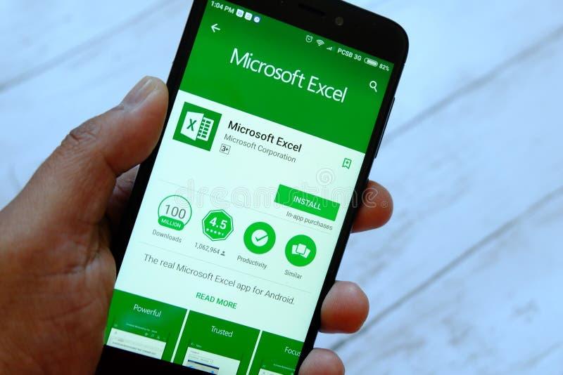 BANDAR SERI BEGAWAN, BRUNEI DARUSSALAM - 25 DE JULHO DE 2018: Uma mão masculina que guarda o smartphone com Microsoft Excel app e imagens de stock
