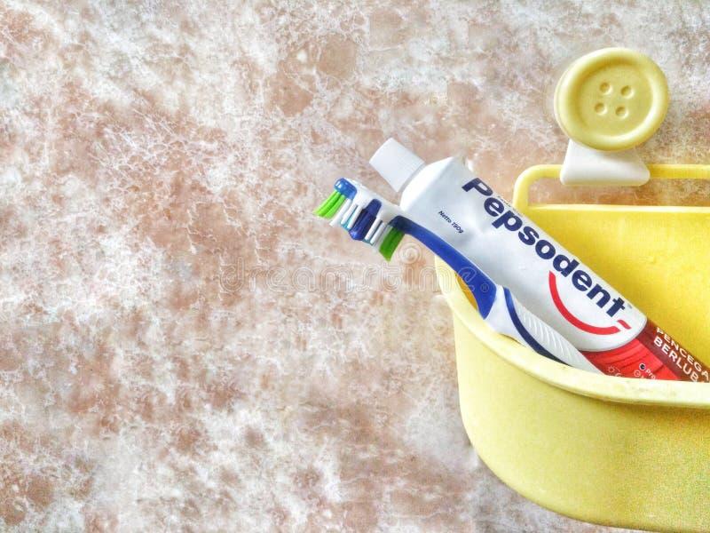Bandar Seri Begawan/Brunei - 19 de mayo de 2019: Imagen del cepillo de dientes y de la crema dental de Pepsodent en un cubo amari imagen de archivo libre de regalías