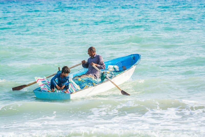 Bandar Siraf, Иран - 20-ое мая 2017 Ветрило отца и сына для удить в Персидском заливе в небольшой голубой шлюпке с сетями fisherm стоковая фотография rf