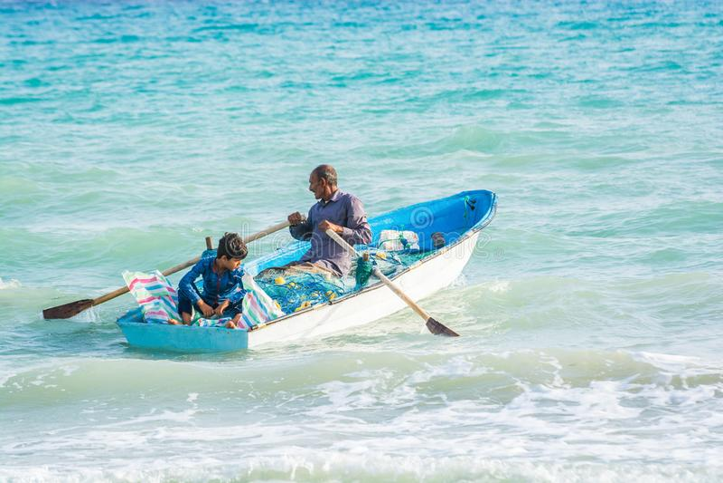 Bandar Siraf, Iran - 20 mai 2017 Voile de père et de fils pour pêcher dans le golfe Persique dans le petit bateau bleu avec des f photographie stock libre de droits