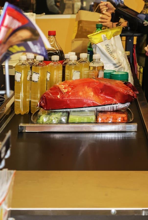 Bande de conveyeur remplie de nourriture au marché d'épicerie avec des sacs étant remplis et des clients non identifiables étant  photos stock
