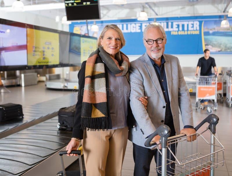 Bande de conveyeur se tenante prêt de couples supérieurs heureux d'affaires chez Airpor photos libres de droits