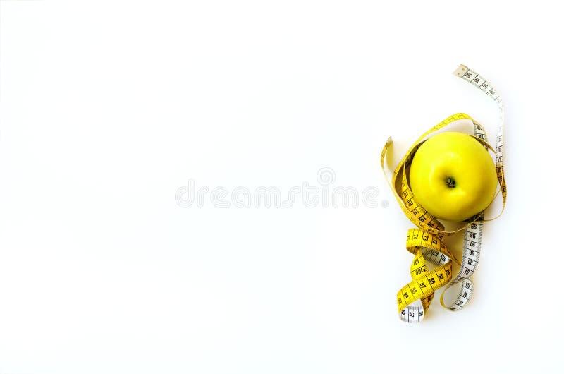 Bande de mesure enroulée autour de la pomme jaune savoureuse fraîche d'isolement sur le fond blanc Régime, perte de poids, forme  image libre de droits