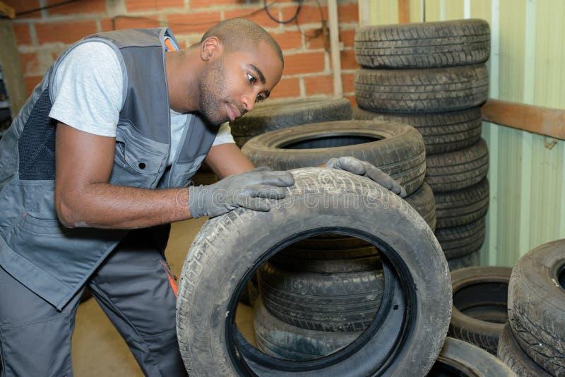 Bande de roulement de examen d'homme sur le pneu démantelé photographie stock libre de droits