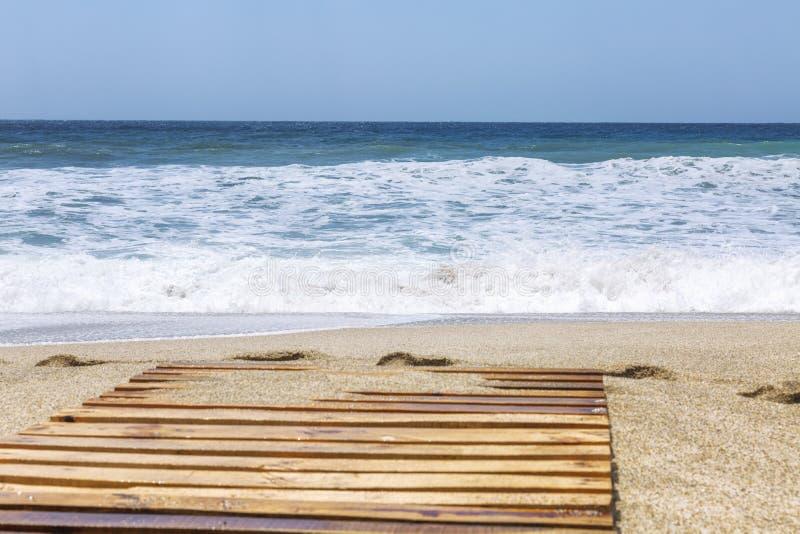 Bande de turquoise de la mer avec des vagues sur une plage sablonneuse Ciel bleu clair Fond Bel horizontal tranquille photographie stock