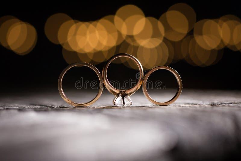 Bande di nozze dell'oro con le luci del bokeh fotografia stock libera da diritti