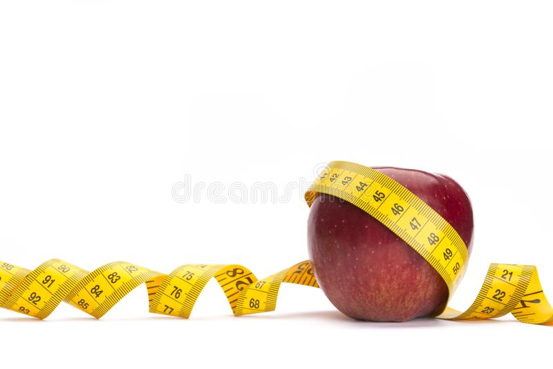 Bande jaune de mesure autour d'une pomme rouge comme concept de perte de poids photo stock
