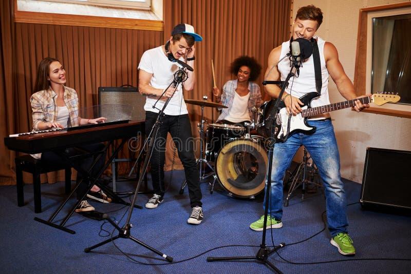 Bande multiraciale de musique exécutant dans un studio d'enregistrement images stock