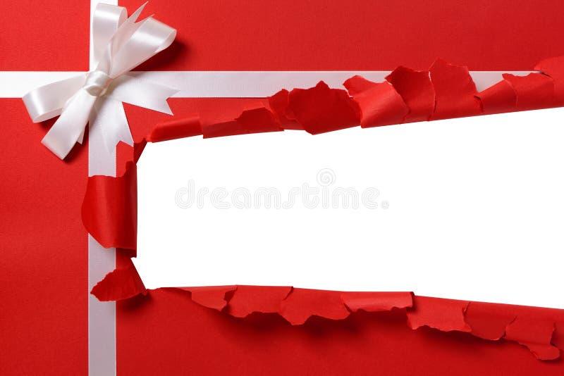 Bande ouverte déchirée par cadeau de Noël, arc blanc de ruban, papier d'emballage rouge photos stock