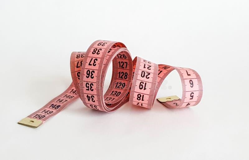 Bande rose de mesure avec des nombres noirs sur un fond naturel blanc Fermez-vous de la bande de mesure Thèmes : régime, fait mai photos stock