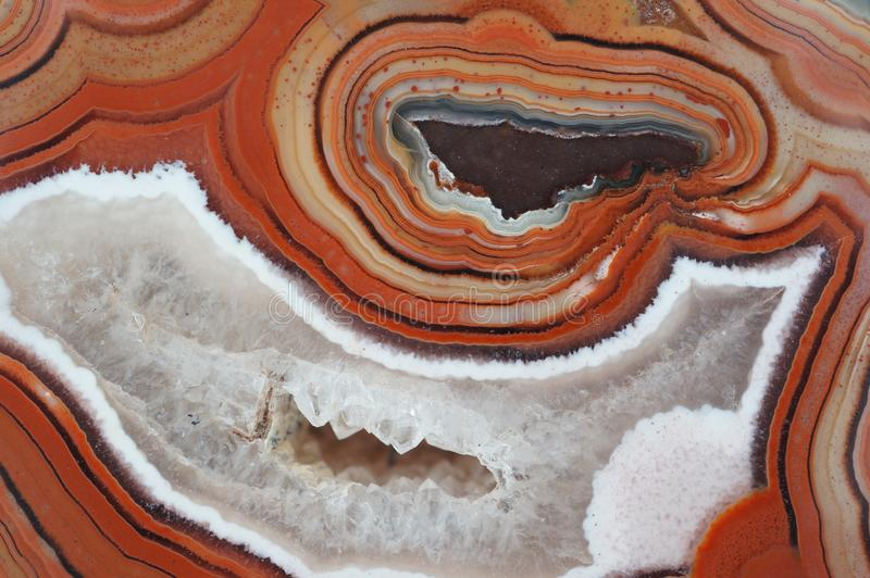 Banded Agate pattern with Quartz geode. Closeup of a banded Agate specimen. The layered structure is formed when a rock cavity or geode is filled with siliceous royalty free stock photography