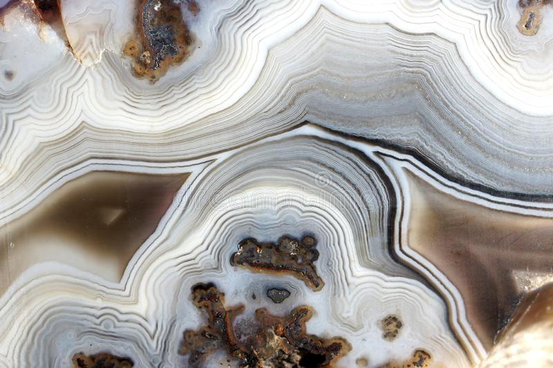 Banded Agate texture. Closeup of a banded Agate specimen. The layered structure is formed when a rock cavity or geode is filled with siliceous matter, layer by stock photography