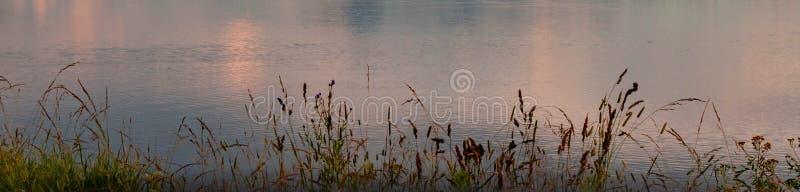 Bandeira alaranjada azul do por do sol do rosa bonito dramático com reflexão do céu e das nuvens no rio pelo medow fotos de stock royalty free