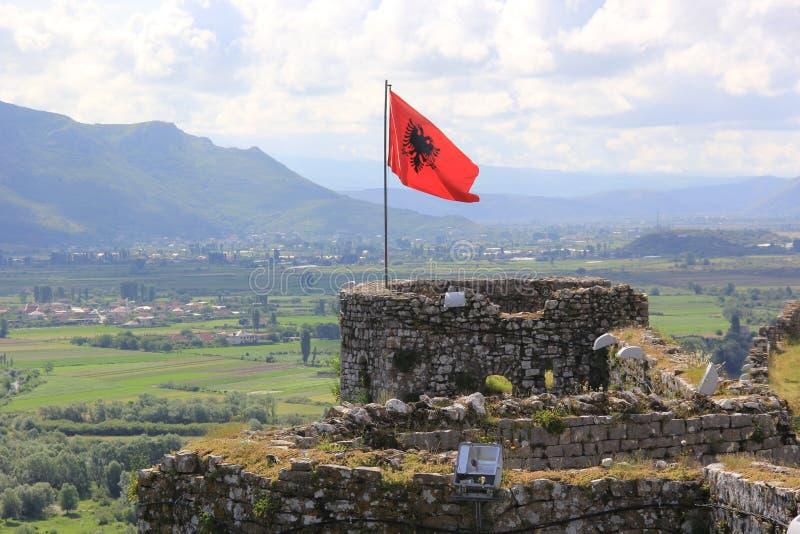 Bandeira albanesa vermelha com uma águia preta dobro-dirigida que acena sobre a parte superior da fortaleza velha Rozafa imagens de stock