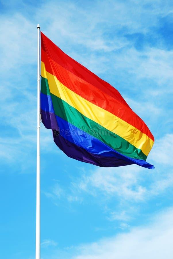 Bandeira alegre do orgulho do arco-íris no céu azul imagens de stock royalty free