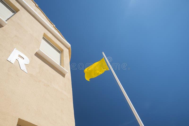 Bandeira amarela na praia imagens de stock