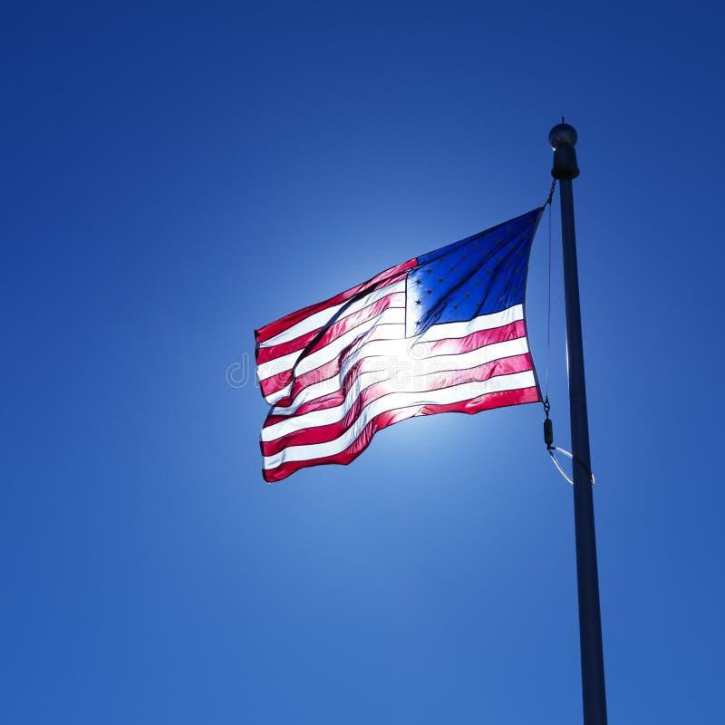 Bandeira americana de ondulação backlit pelo sol. fotos de stock