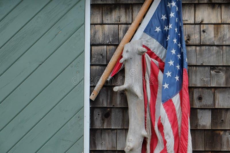 A bandeira americana drapejou sobre uma parte de madeira lançada à costa fotografia de stock