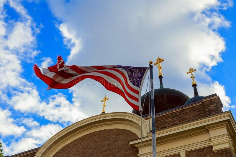 A bandeira americana e a torre velha da igreja refletem a separação de estado foto de stock