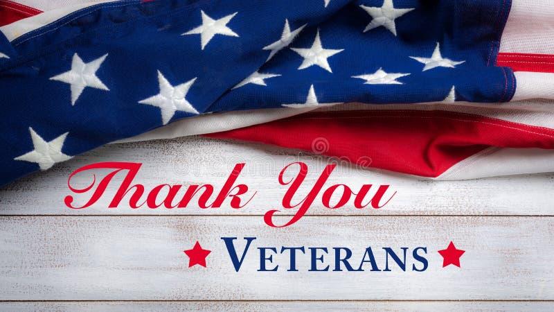 Bandeira americana em um fundo de madeira vestido branco com cumprimento do dia do ` s do veterano imagem de stock