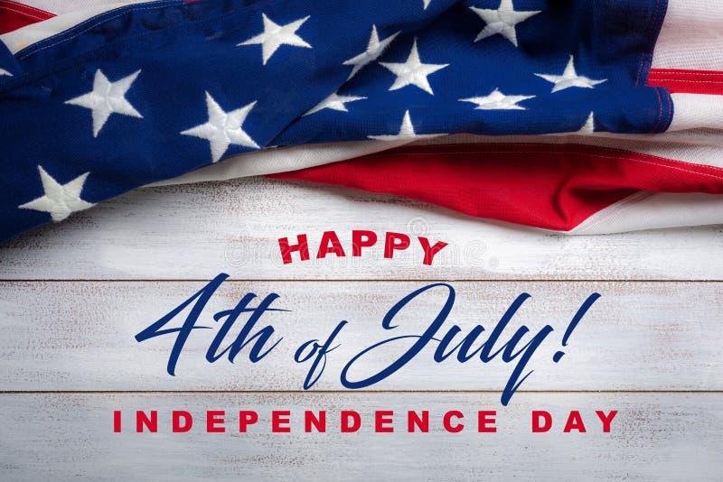 Bandeira americana em um fundo de madeira vestido branco com cumprimento do 4 de julho imagens de stock royalty free