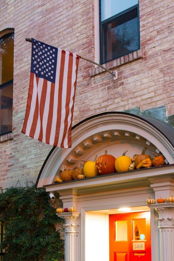 A bandeira americana em uma fachada decorada com abóboras de Dia das Bruxas foto de stock