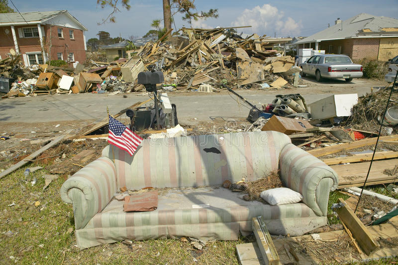 A bandeira americana no sofá e nos restos na frente da casa bateu pesadamente pelo furacão Ivan em Pensacola Florida imagem de stock royalty free