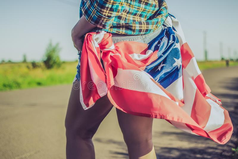 Bandeira americana nos quadris do ` s da menina como um símbolo da liberdade e da escolha fotografia de stock royalty free