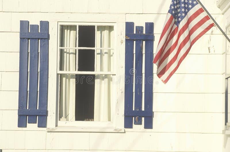 Bandeira americana pendurada em uma casa branca, Stonington, Maine imagem de stock royalty free