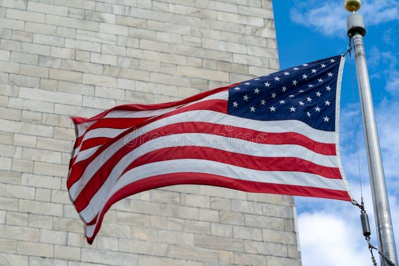 Bandeira americana que funde no vento com Washington Monument ao longo do National Mall C?u em parte nebuloso imagens de stock royalty free