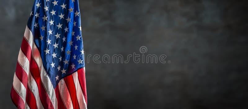 Bandeira americana que pendura livremente contra uma parede escura imagem de stock
