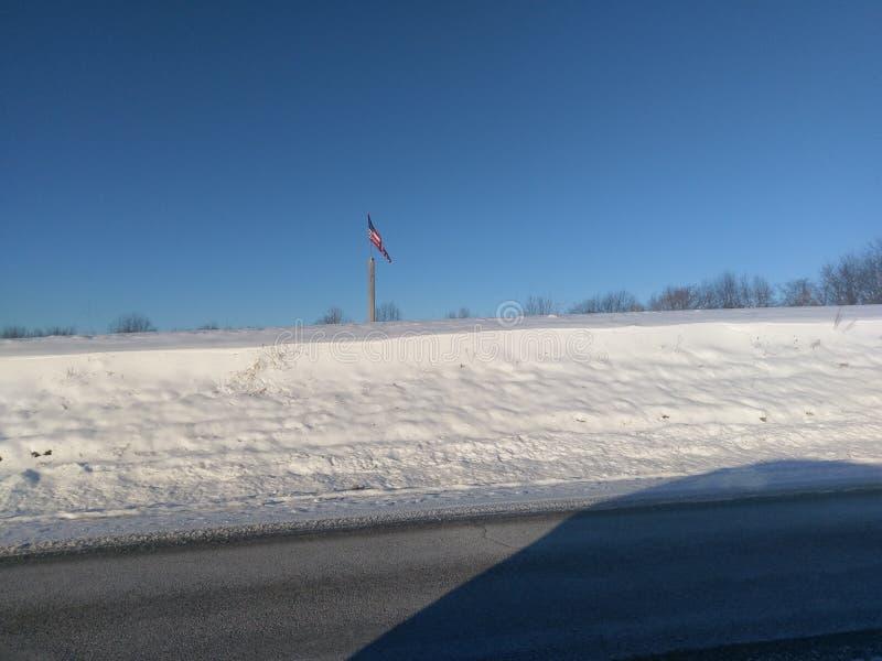 Bandeira americana sobre o snowbank ao longo da estrada 55 do estado imagens de stock