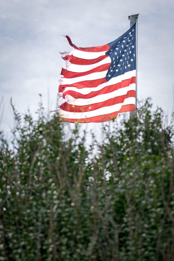 Bandeira americana, &Stripes das estrelas, esfarrapados e desgastados na borda, fundindo no vento em um dia cinzento e sombrio, c foto de stock royalty free