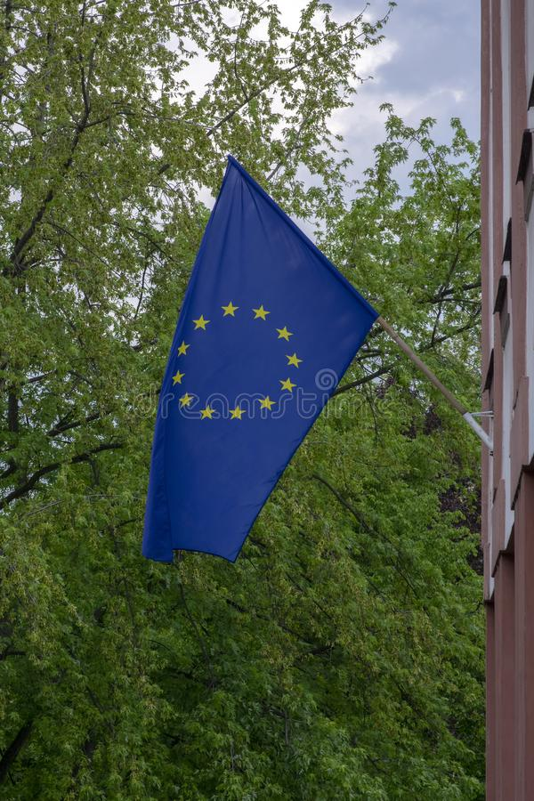 A bandeira azul com os doze amarelos protagoniza no vento contra o c?u azul e a folha verde das ?rvores imagem de stock royalty free