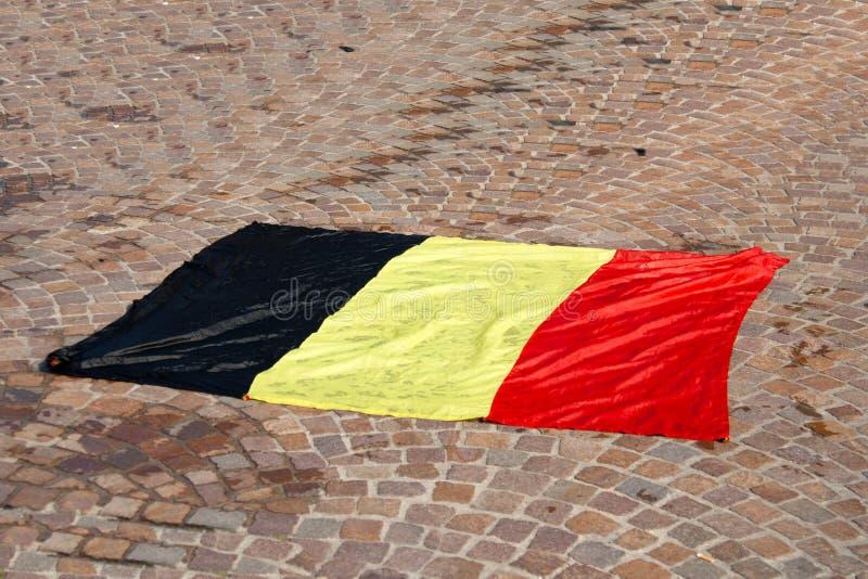 Bandeira belga molhada que encontra-se no pavimento imagens de stock