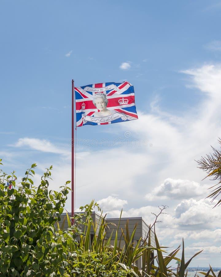 A bandeira britânica com Elizabeth II da rainha enfrenta nela imagens de stock royalty free