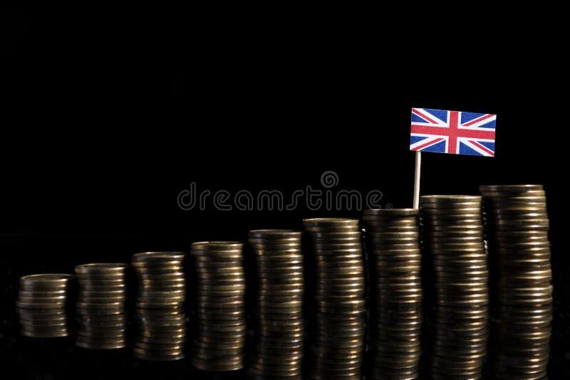 Bandeira BRITÂNICA com lote das moedas no preto imagem de stock royalty free