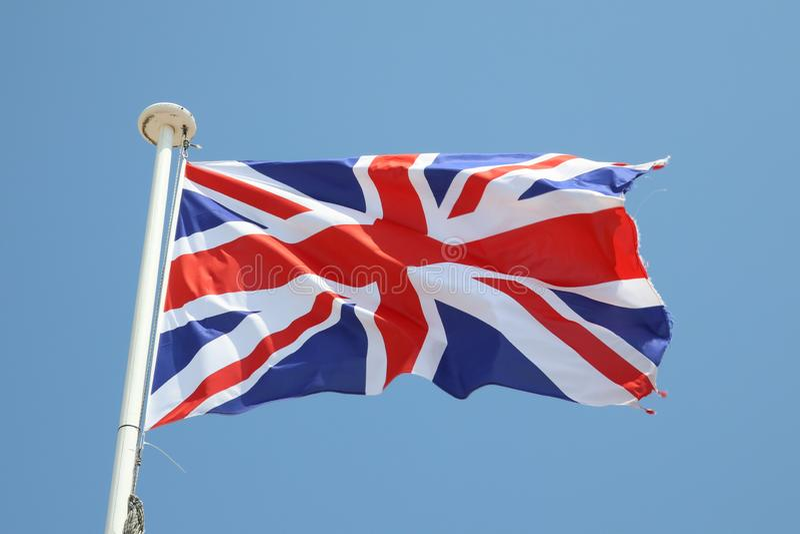 bandeira britânica em uma esteira no vento e no céu azul imagem de stock